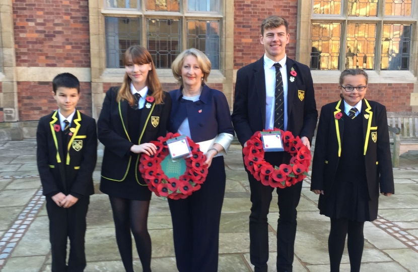 Mary Robinson pictured holding a wreath with pupils of Stockport Grammar